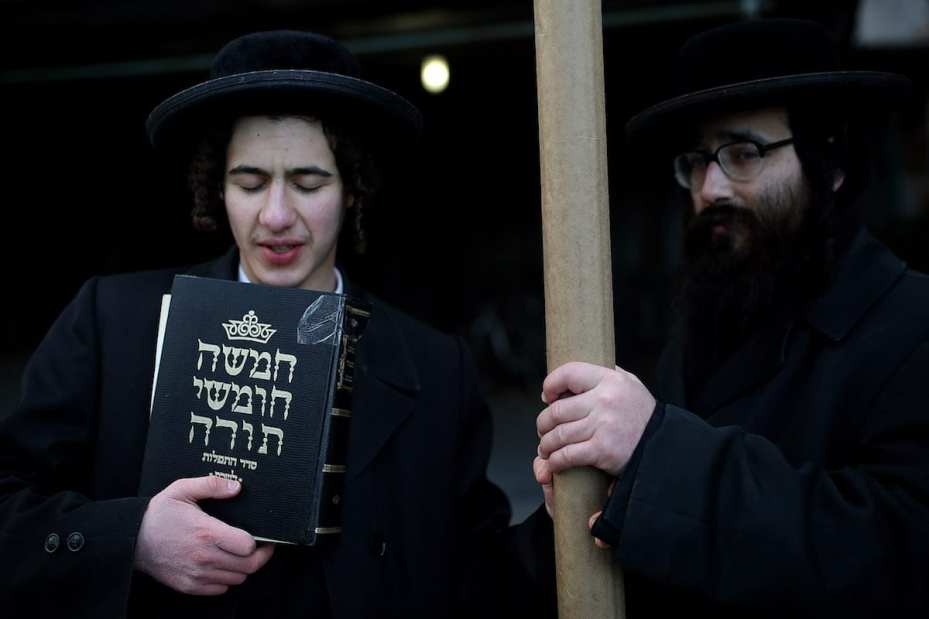 NEW YORK, UNITED STATES - DECEMBER 28: A member of Orthodox Jews holds a copy of the Talmud during a protest to celebrate UN decision to condemn Israeli settlements outside the United Nations headquarters in Manhattan borough of New York City, USA on December 28, 2016. ( Mohammed Elshamy - Anadolu Agency )
