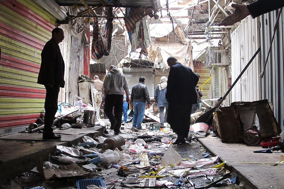 BAGHDAD, IRAQ - DECEMBER 31: People inspect the scene of twin suicide attacks at a bazaar in Baghdad, Iraq on December 31, 2016. At least 24 people were killed and dozens injured in a twin bombing claimed by Daesh.