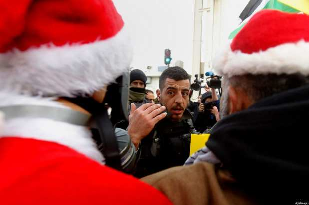 A Palestinian protester dressed up as Santa Claus argues with Israeli border guard during clashes at a demonstration next to a section of Israel's separation wall in the biblical town of Bethlehem, in the occupied West Bank, on December 23, 2016 [Wisam Hashlamoun / ApaImages]