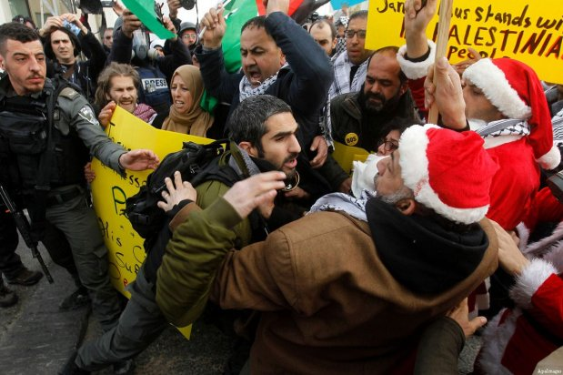 An Israeli border policeman scuffles with a Palestinian protester dressed up as Santa Claus during clashes at a demonstration next to a section of Israel's separation wall in the biblical town of Bethlehem, in the occupied West Bank, on December 23, 2016 [Wisam Hashlamoun / ApaImages]