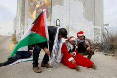 A Palestinian protester dressed up as Santa Claus reacts after inhaling tear gas fired by Israeli border guard during clashes at a demonstration next to a section of Israel's separation wall in the biblical town of Bethlehem, in the occupied West Bank, on December 23, 2016 [Wisam Hashlamoun / ApaImages]