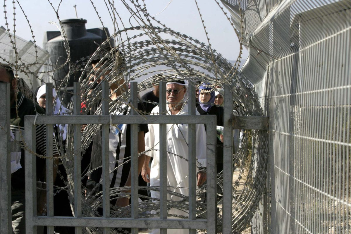 Palestinians wait to cross the Israeli checkpoint in West Bank [APA Images]