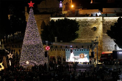 Palestinian watch fireworks marking the lighting of a Christmas tree on December 3, 2016 at the Manger Square near the Church of the Nativity, in the West Bank town of Bethlehem [Wisam Hashlamoun / ApaImages]