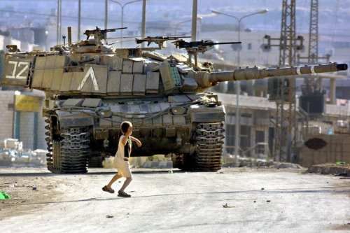 A Palestinian child throws stones at an Israeli Defence Force's tank, much like the iconic image of Faris Odeh from October 2000, during the First Intifada