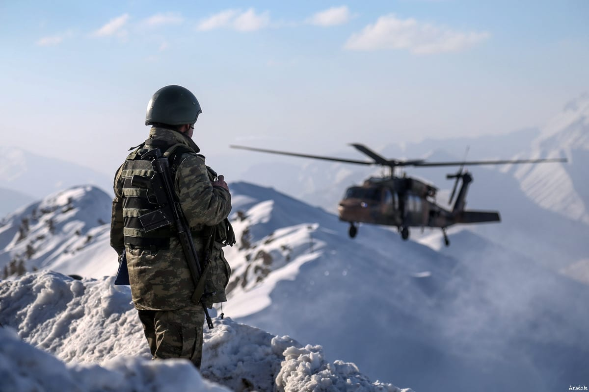 A Turkish soldier keeps watch as a military helicopter flies by during an operation against the PKK in Hakkari, Turkey on December 30, 2016 [Özkan Bilgin / Anadolu Agency]
