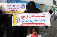 RAFAH, GAZA - JANUARY 3: A group of protesters hold banners during a demonstration demanding opening of a new hospital in Rafah in front of en-Neccar Hospital in Rafah, Gaza on January 3, 2017. ( Abed Rahim Khatib - Anadolu Agency )