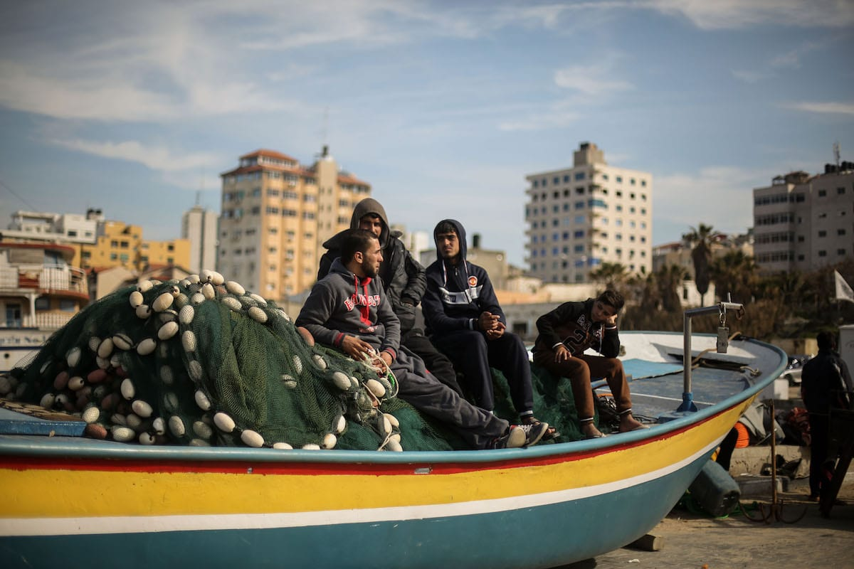 Fishermen sit together on a fishing boat at a shore in Gaza City, Gaza [Mohammed Talatene/Anadolu Agency]