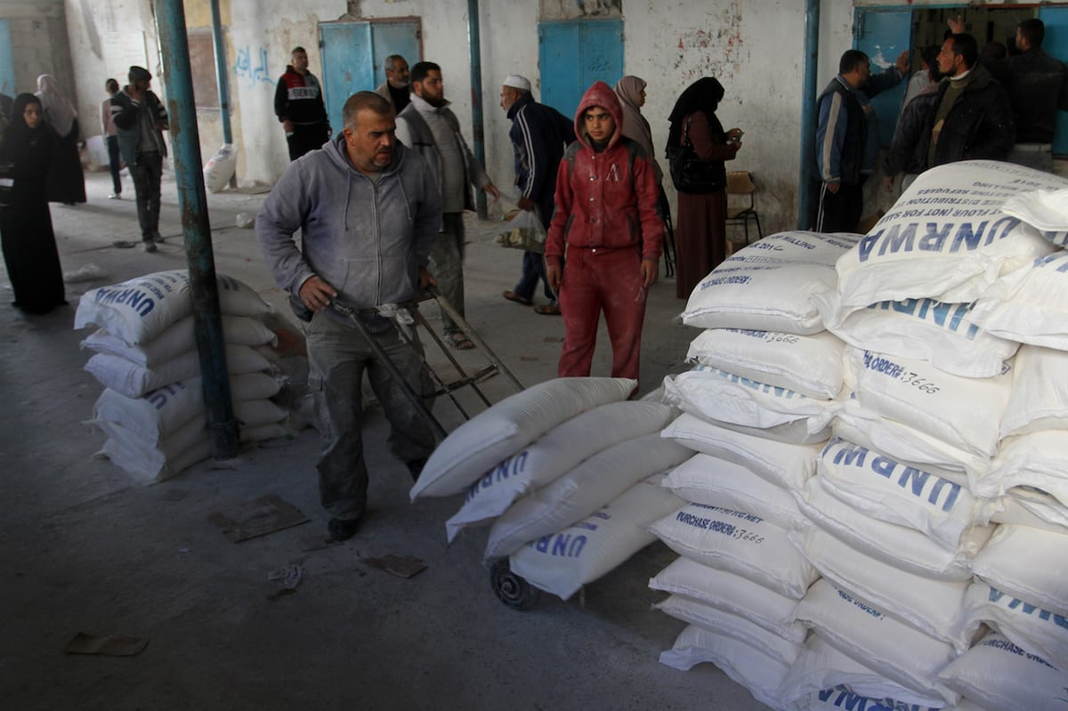 A Palestinian man carries sacks of flour during a food aid distribution by UNRWA in Rafah, Gaza on 22 January 2017 [Abed Rahim Khatib/Anadolu Agency]