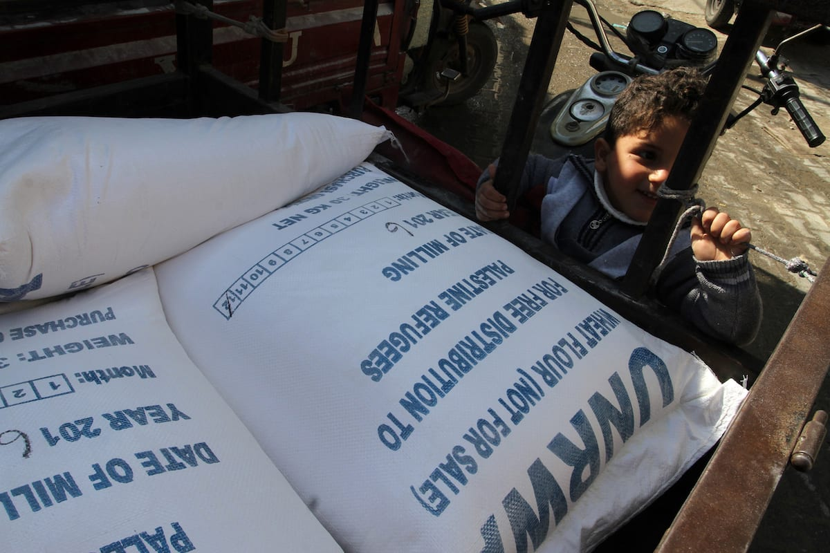 A Palestinian child stands next to the food aid given by UNRWA in Rafah, Gaza on 22 January 2017 [Abed Rahim Khatib/Anadolu Agency]