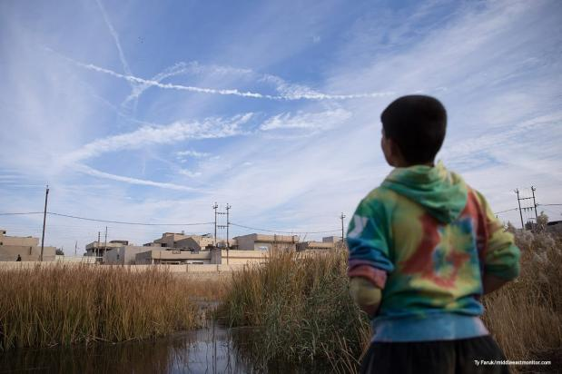 A young boy looks to the sky watching US fighter jet trails as they circle the city [Ty Faruk/middleeastmonitor.co]