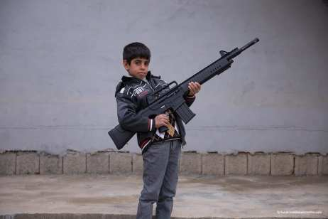 A boy holds his father's weapon in the rural village of Qashqa, Iraqi Kurdistan [Ty Faruk/middleeastmonitor.com]