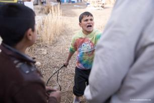 The same young boy threatens to whip a grown man with a tyre tube accusing him of looting. Later on he throws stones to ward off groups of younger boys his own age [Ty Faruk/middleeastmonitor.co]