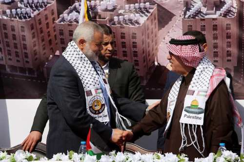 Hamas leader Ismail Haniyeh shakes hands with Qatar's Ambassador to the Palestinian Authority, Mohammed Al Emadi during the ceremony of the second phase of the Sheikh Hamad Town, in Khan Younis in the southern Gaza strip, on February 11, 2017 [Ashraf Amra / ApaImages]