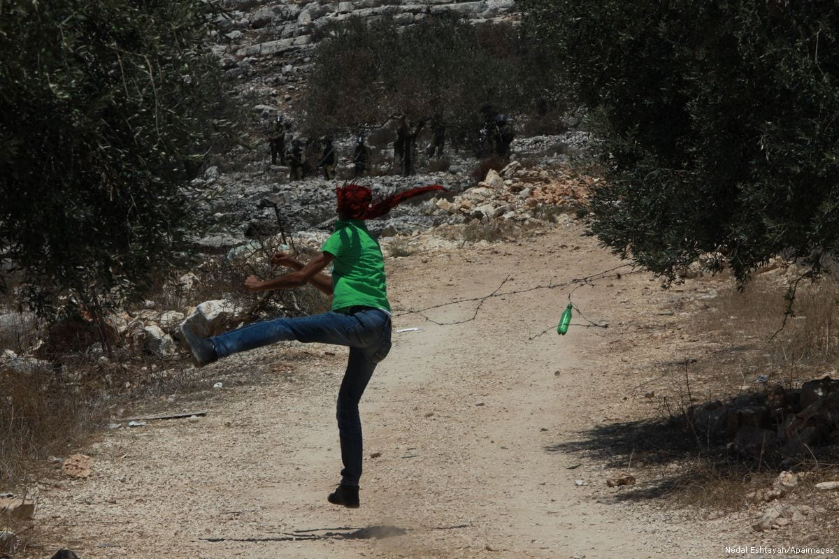 Palestinian protesters throw stones at Israeli soldiers during clashes in Nablus, West Bank [Nedal Eshtayah/Apaimages]