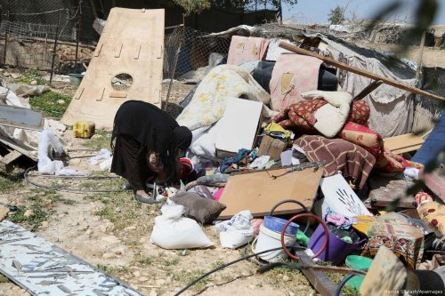 Palestinian women inspects the debris in al-Khan al-Ahmar after Israeli authorities ordered the demolition of her home [Hamza Shalash/Apaimages]