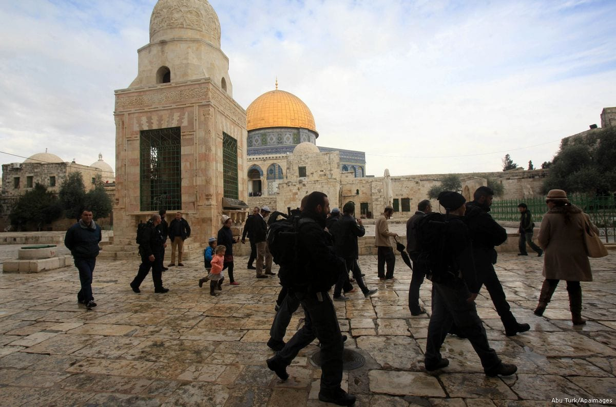 Jewish settlers are protected by Israeli security forces as they enter the Al-Aqsa mosque compound [Mahfouz Abu Turk/Apaimages]