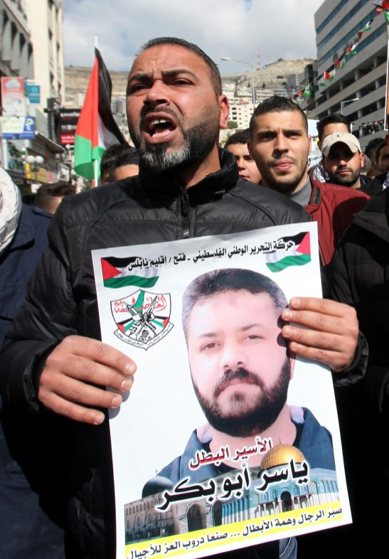 NABLUS, WEST BANK - FEBRUARY 6: A protester holds a banner containing his relative picture during a demonstration demanding the release of the Palestinians, held in Israeli prisons, in Nablus, West Bank on February 6, 2017. ( Nedal Eshtayah - Anadolu Agency )