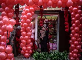 GAZA CITY, GAZA - FEBRUARY 14: A Palestinian woman is seen in front of a decorated souvenir gift shop on Valentine's Day in Gaza City, Gaza on February 14, 2017. ( Ali Jadallah - Anadolu Agency )