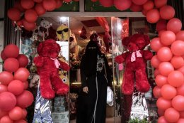 Palestinian woman is seen in front of a decorated souvenir gift shop on Valentine's Day in Gaza City, Gaza on 14 February, 2017 [Ali Jadallah/Anadolu Agency]
