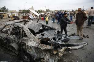 BAGHDAD, IRAQ - FEBRUARY 17: Men inspect the wreckage of cars a day after a car bomb attack at al-Bayaa auto gallery in capital of Baghdad, Iraq on February 17, 2017. Many casualities reported after the attack. ( Murthadha Sudani - Anadolu Agency )