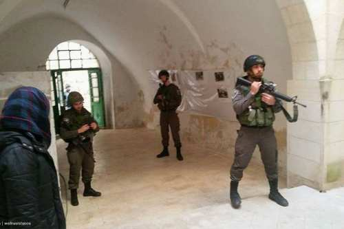 Israeli forces stand guard after breaking into the office of Palestinian government's Colonisation and Wall Resistance Commission (CWRC) in the Old City of occupied Hebron [Facebook]