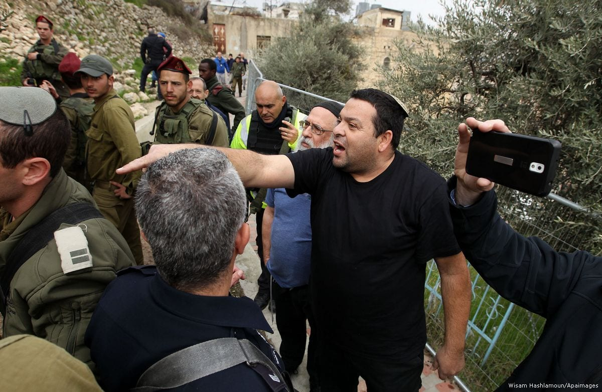 Israeli forces stand in front of Jewish settlers who are harassing Palestinians in the West Bank [Wisam Hashlamoun/Apaimages]