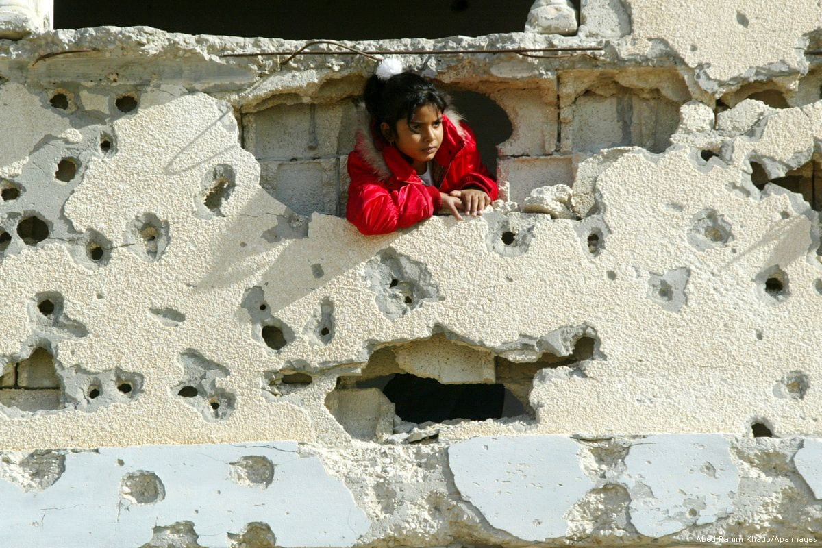A Palestinian child stands on the destroyed window of her home which was demolished during Israel's offensive on Gaza [Abed Rahim Khatib/Apaimages]
