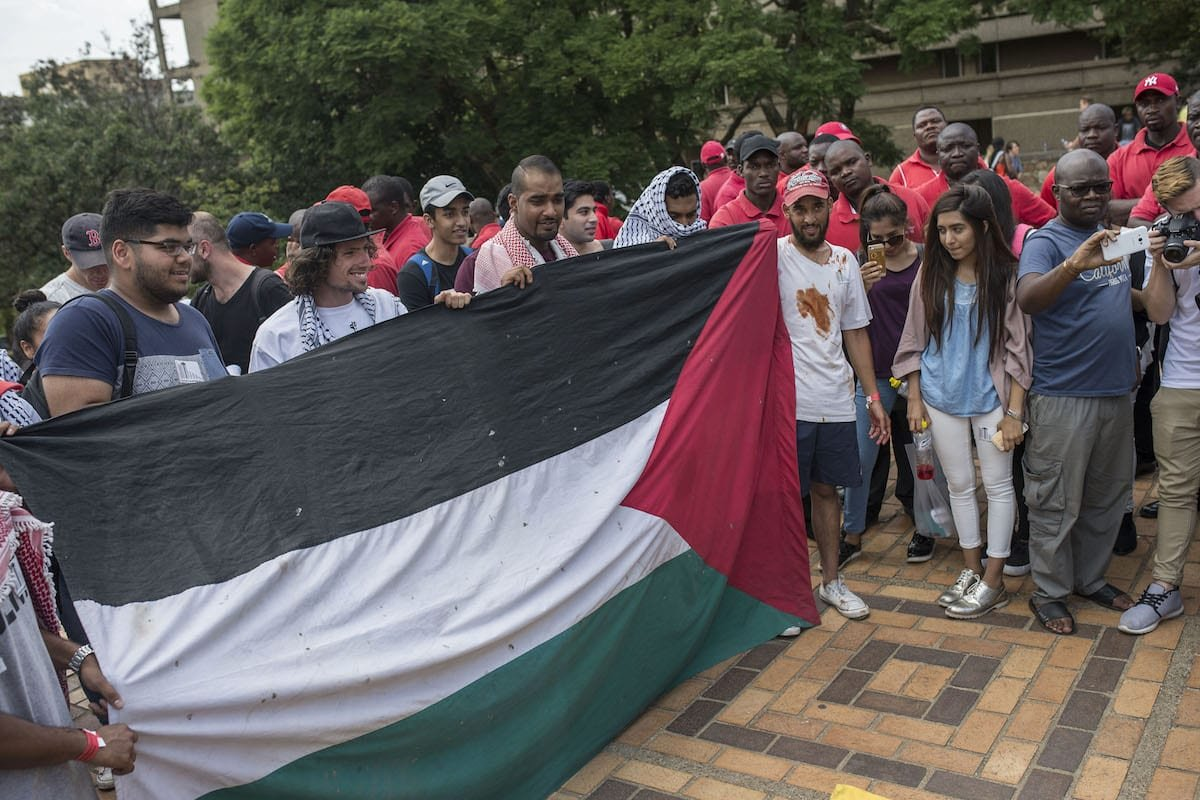 A group of students hold a Palestinian flag during a protest against Israel's policies at Witwatersrand University in Johannesburg, South Africa on March 8, 2017 [Ihsaan Haffejee/Anadolu Agency]