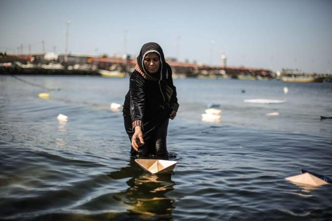 Palestinian woman releases paper ships, reading 'Save the Gazan Women' and 'We Want Honourable Life' to the sea to draw attention to Israeli blockade on Gaza on March 09, 2017 [Mohammed Talatene / Anadolu Agency]