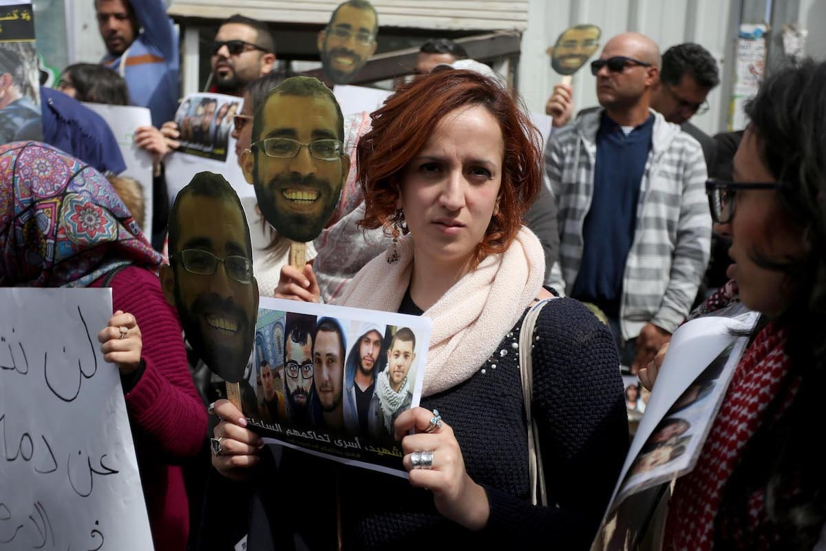 Palestinians hold banners as they gather to protest against the trial of Basel al-Araj, who was killed during a raid by Israeli soldiers at his home, and his five friends in front of the Ramallah Minor Court in Ramallah, West Bank on March 12, 2017. Their dead bodies have not been returned to their families. Basel and his friends are being judged for possession of an unregistered firearm [Issam Rimawi / Anadolu Agency]