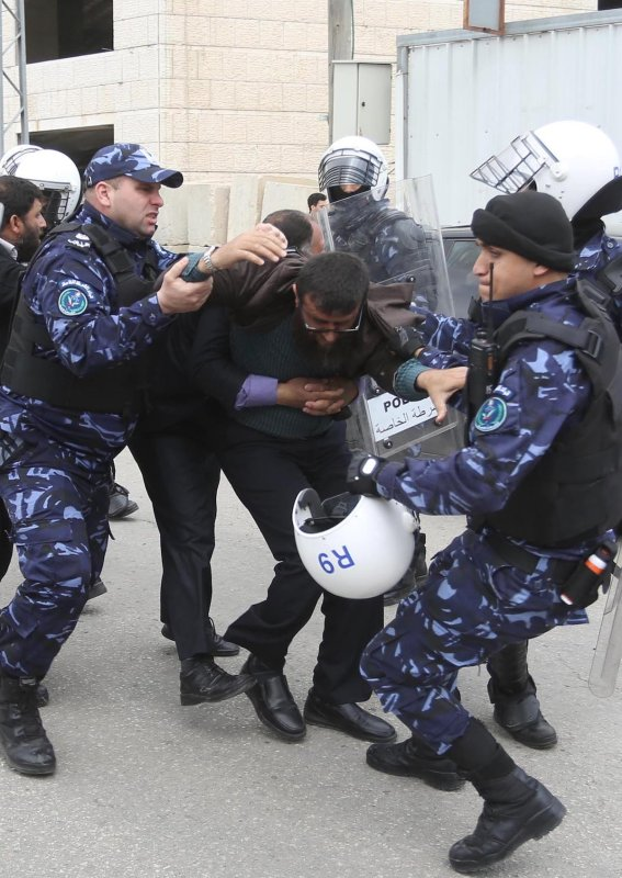 Palestinian Authority police forces can be seen violently arresting a Palestinian man on 12 March 2017 [Issam Rimawi/Anadolu Agency]