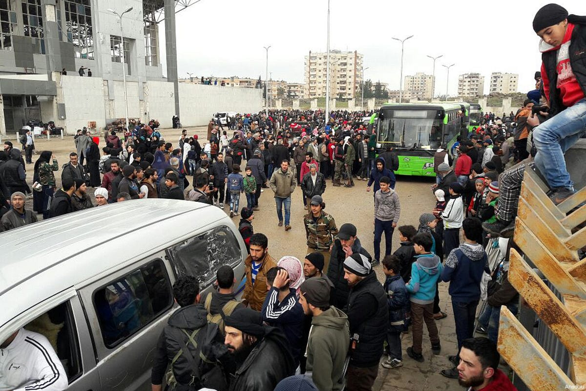 Syrian opposition members and their families gather to get into buses during an evacuation from the al-Waer neighbourhood, in the western outskirts of the central city of Homs, Syria on March 18, 2017. [Stringer / Anadolu Agency]