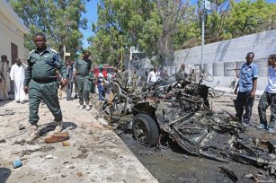 MOGADISHU, SOMALIA: People and security forces can be seen near a damaged vehicle is seen at the explosion site after a car bomb exploded near the Presidential Palace in Mogadishu, Somalia on March 24, 2017. [Sadak Mohamed/Anadolu Agency]