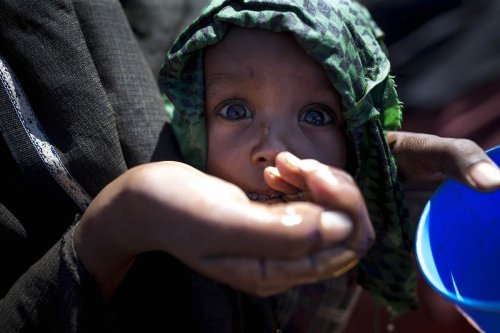 A Somalian woman gives her child water from her palm at Dakamur camp in Somalia's Bay state on March 27, 2017 (Arif Hüdaverdi Yaman - Anadolu Agency )
