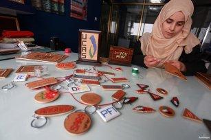 GAZA CITY, GAZA- Noor Jaber works embroidering patterns on wood at her workshop