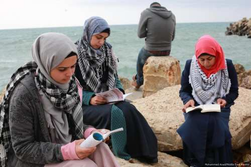 Palestinians organise a reading chain in Gaza seaport in memory of intellectual martyrs who were killed by Israeli forces [Mohammed Asad/Middle East Monitor]