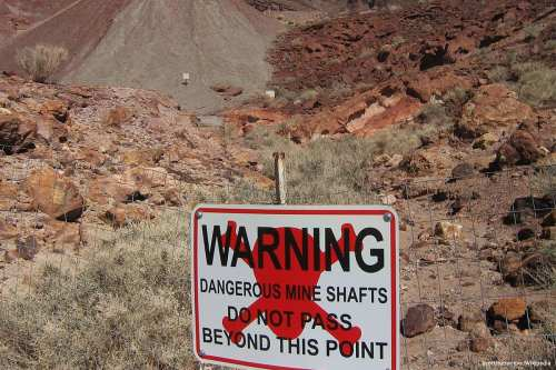 Image of a sign warning people of dangerous mines in the area [Scottthezombie/Wikipedia]