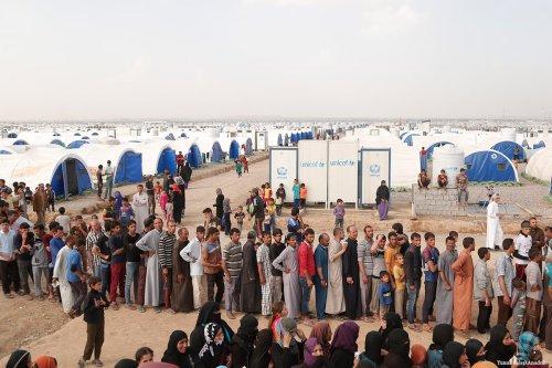 Internally displaced Iraqi civilians wait in a line to receive humanitarian aid in Nineveh, Iraq on 29 March 2017 [Yunus Keleş/Anadolu]