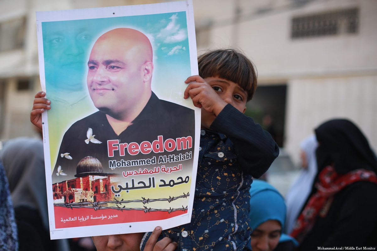 Gaza-based staff and beneficiaries of World Vision rally in support of the organisation's jailed Gaza director, Mohammad al-Halabi, on March 28, 2017 [Mohammed Asad / Middle East Monitor]