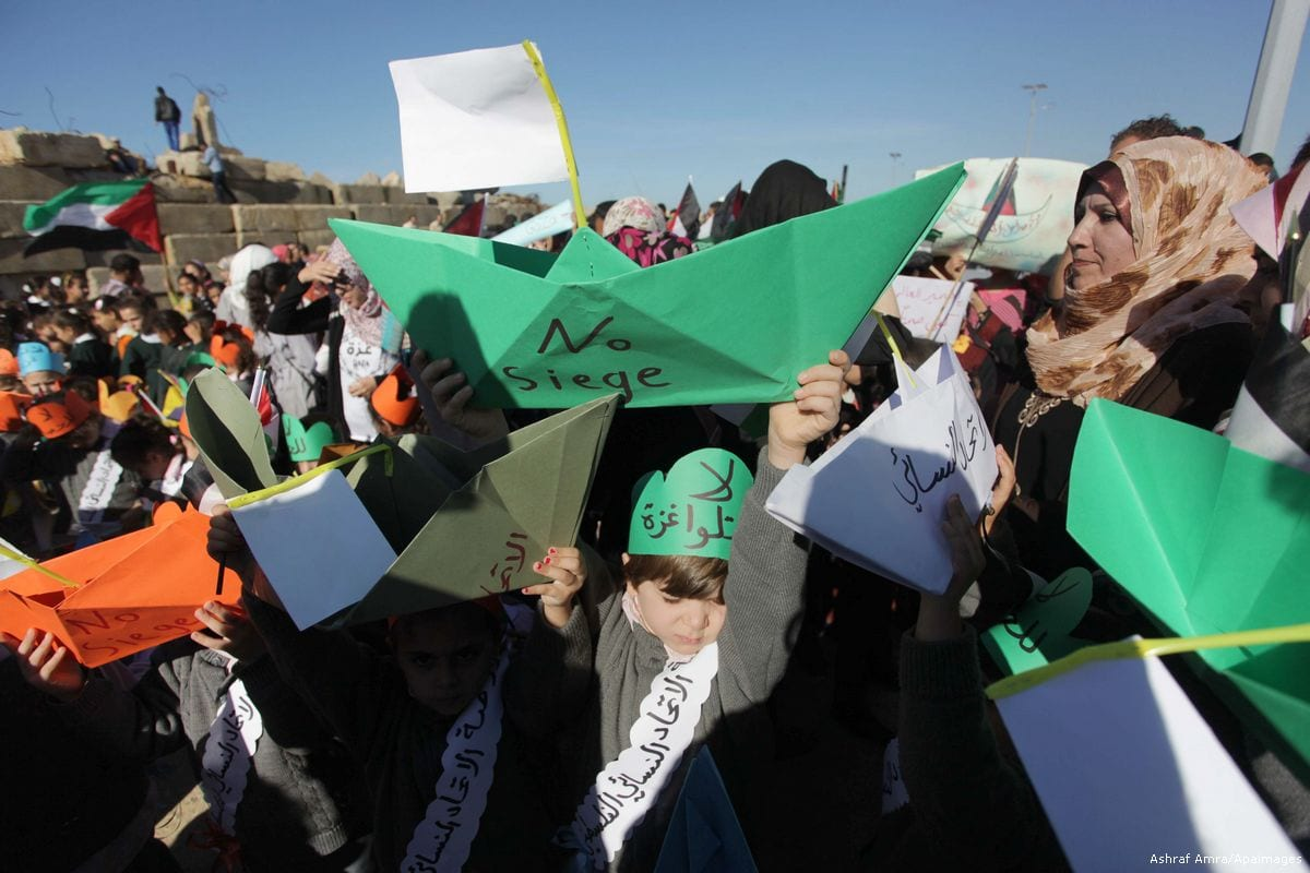 """Palestinian children hold paper ships reading in Arabic """"No to the siege"""" during a rally to protest against the Israeli siege of the Gaza Strip [Ashraf Amra/Apimages]"""
