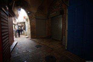 An old woman passes by a closed shop in Jerusalem after a general strike was to show solidarity with Palestinian prisoners in Israeli jails in Jerusalem on April 27, 2017. ( Mostafa Alkharouf - Anadolu Agency )