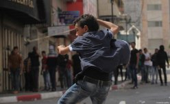 HEBRON, WEST BANK - APRIL 27: A Palestinian boy uses a sling to throw stones at Israeli Security Forces after they intervened a demonstration held in support of Palestinian prisoners in Israeli jails, in Hebron, West Bank on April 27, 2017. ( Mamoun Wazwaz - Anadolu Agency )