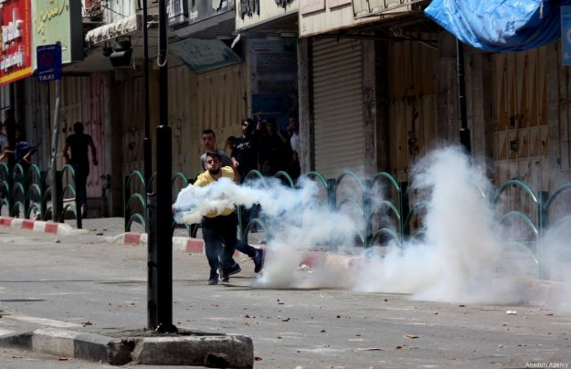A Palestinian man throws a tear gas canister back at during a demonstration held in support of Palestinian prisoners in Israeli jails, in Hebron, West Bank on April 27, 2017. ( Mamoun Wazwaz - Anadolu Agency )