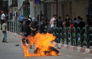Palestinians burn tires after Israeli Security Forces intervene during a demonstration in support of Palestinian prisoners in Israeli jails, in Hebron, West Bank on April 27, 2017. ( Mamoun Wazwaz - Anadolu Agency )
