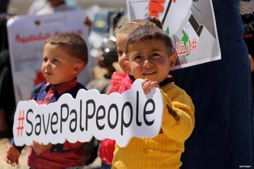"""Palestinian activists take part in a rally titled """"Save Pal People"""" against the Israeli occupation and Gaza blockade in front of a tower which was destroyed during the 50-day war between Israel and Hamas in the summer of 2014"""