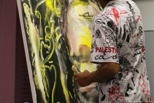 Image of Palestinian artist Salim Assi who spent the evening painting on a canvas as performances took place on 10 April 2017 [Jehan Alfarra/Middle East Monitor]