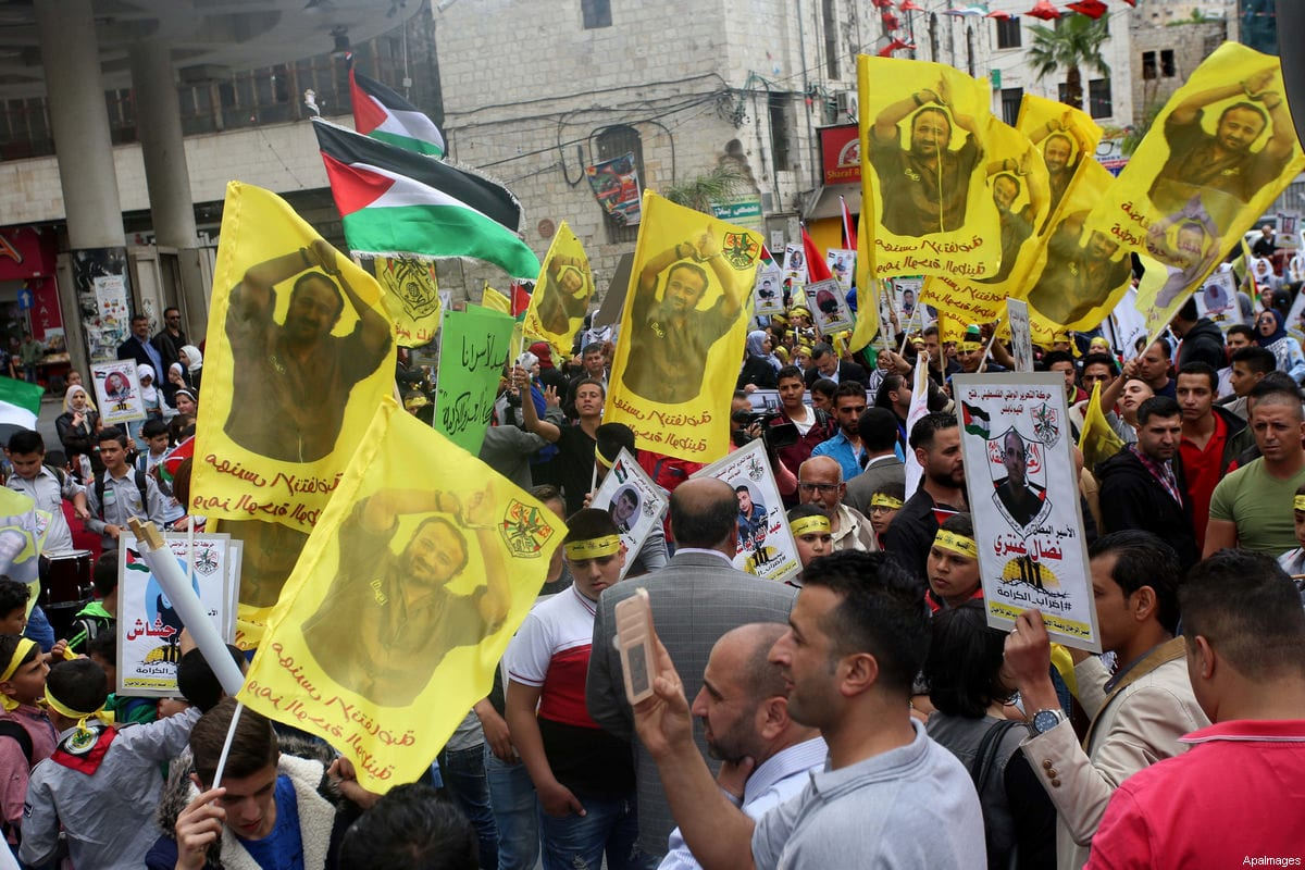 Palestinian protesters wave flags bearing the portrait of prominent prisoner and popular leader Marwan Barghouti during a demonstration in solidarity with Palestinian prisoners on hunger strike in Israeli jails, in West Bank on 23 April, 2017 [Ayman Ameen / ApaImages]