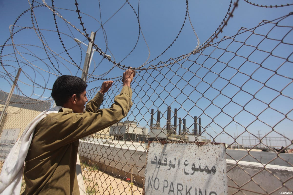 A Palestinian youth stands behind barbed wires surrounding the power station in Gaza on 29 July 2015 [Ashraf Amra / ApaImages]