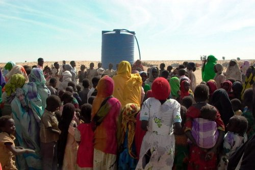 Displaced persons at a water tank in West Darfur, Sudan [Nite Owl/Wikipedia]