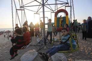 Children play at the fair in Gaza as the electricity crisis forces families outdoors in the evenings and weekends on 29 April in Gaza. [Image: Mohammad Asad / Middle East Monitor]
